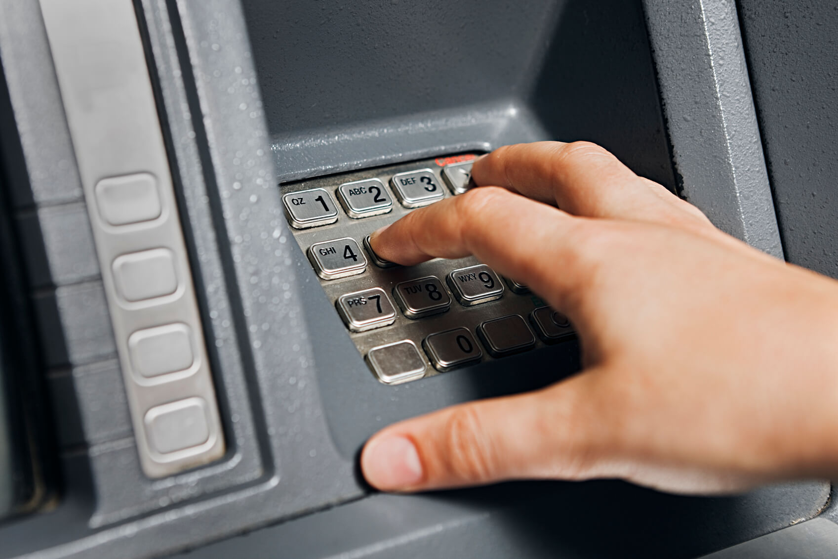 Close up on a woman's hand as she enters numbers on an ATM keypad. Shot with Canon EOS 1Ds Mark III.