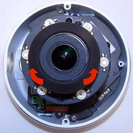 A dome IP camera sensor with arrows showing how to adjust the sensor in a clockwise position during IP camera set up