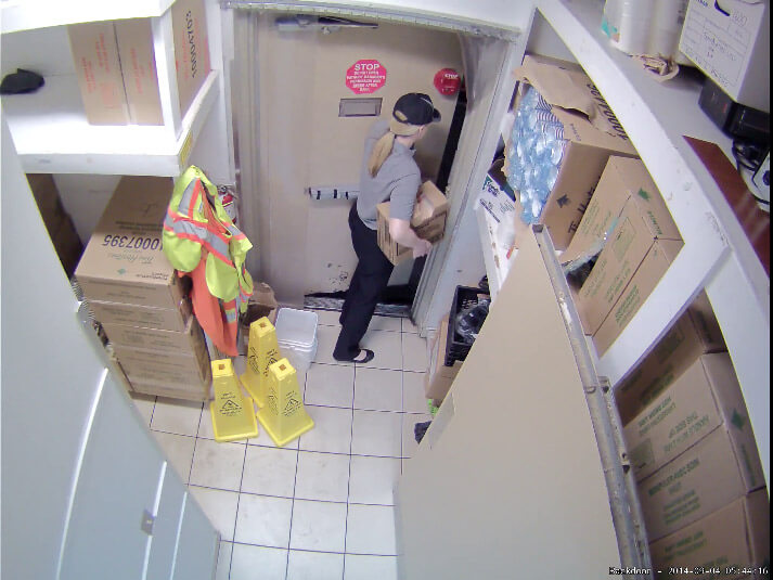 a woman carries a box out the back door of a restaurant. Video surveillance can help uncover employee theft