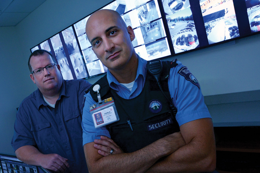 two security officers stand in front of a video wall displaying surveillance video at Hamilton Health Sciences