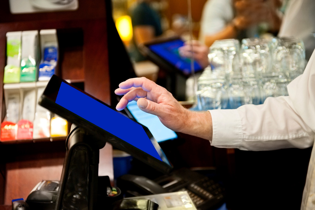 a person's hands hover over the touch-screen of a point-of-sale system in a restaurant