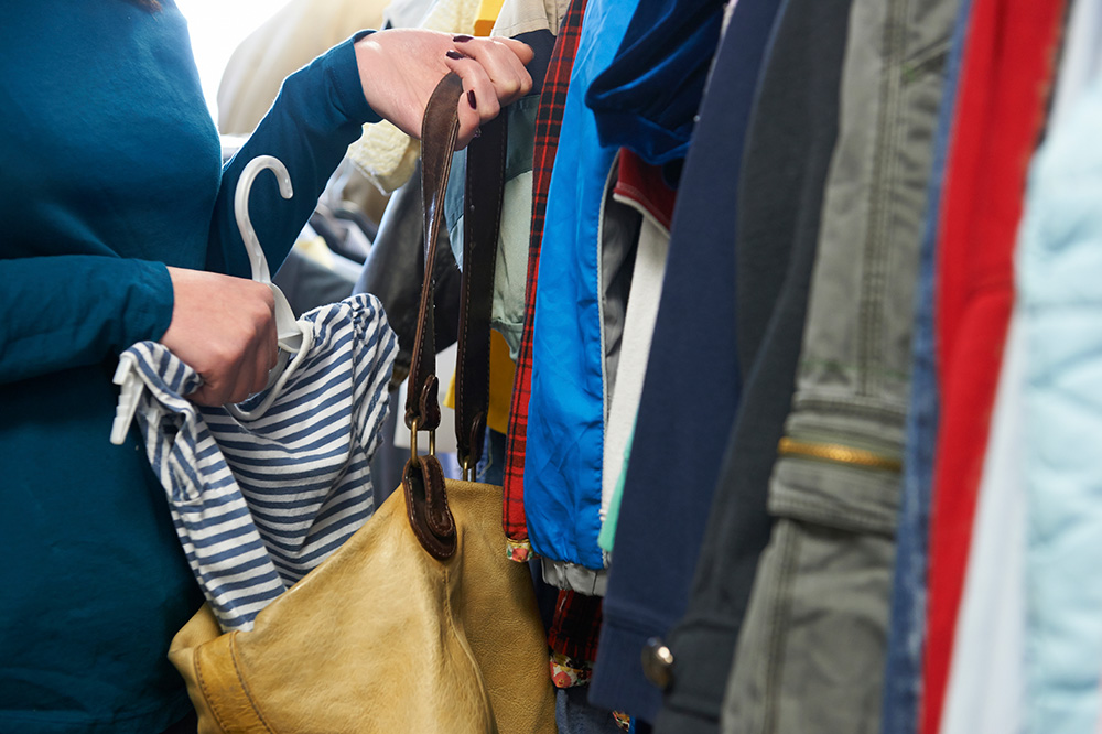 a woman stuffs clothing into her purse