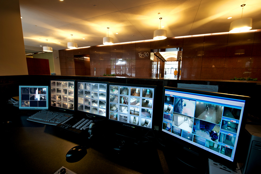 a row of computer monitors display multiple surveillance images