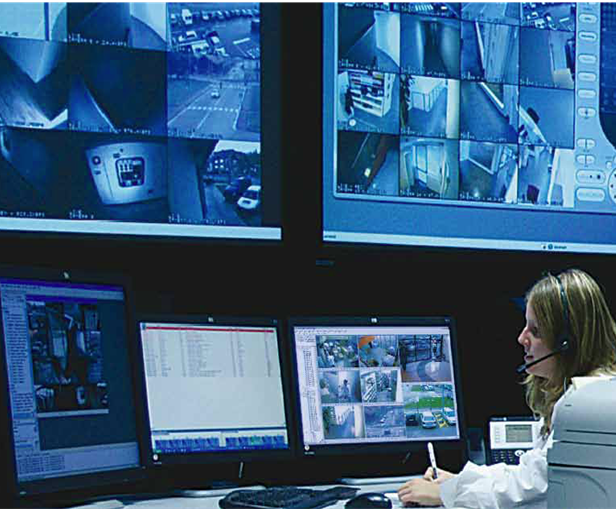 a woman with a headset on sits at a desk with 3 computer monitors displaying video surveillance footage. A video wall with more surveillance video on the screen is seen above her.