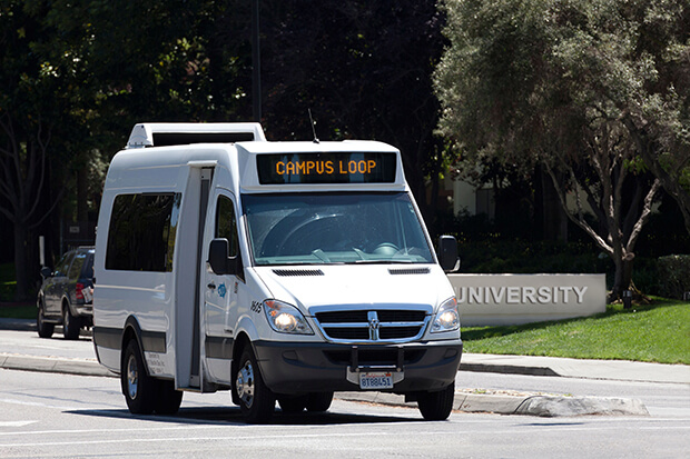 a campus shuttle bus drives near a university