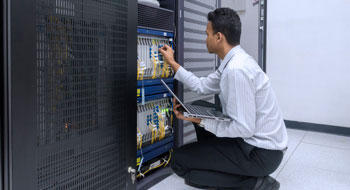 A technician sits with his laptop and works on a stack of servers.