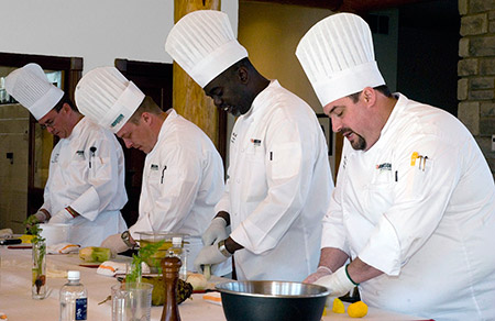 Compass Group chefs – Four chefs work at a table preparing food.