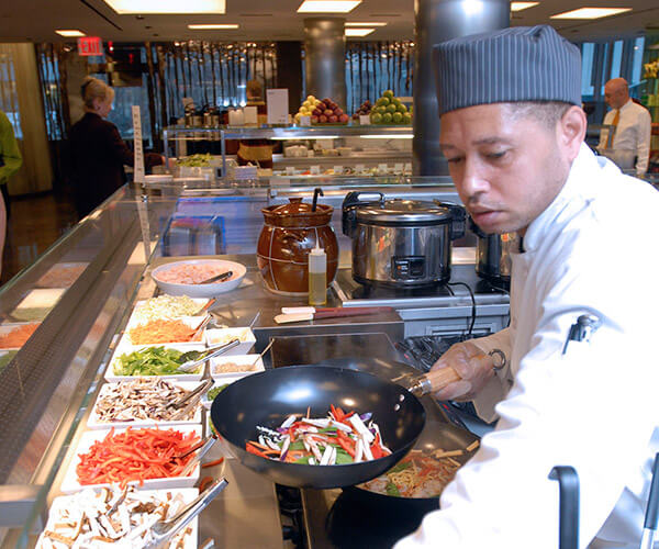 a man in a chef's hat stands over a counter with food