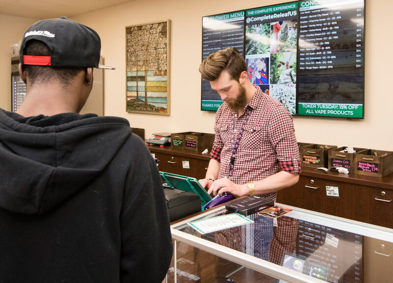 two men stand at the dispensary counter at the Complete Releaf cannabis dispensary in Lafayette, Colorado.