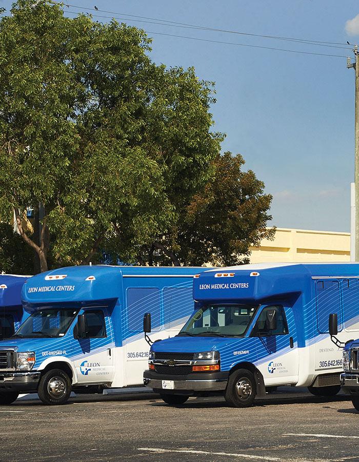 Four Leon Medical Centers passenger vans sit in a parking lot.