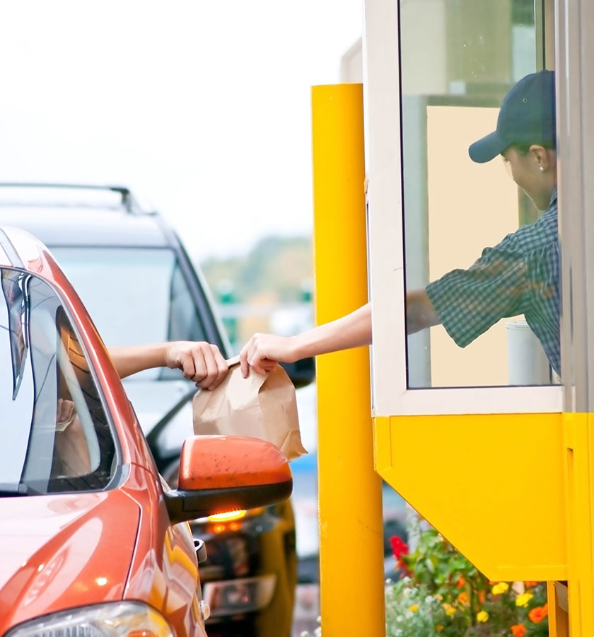 A woman hands over food to a customer in a car in a fast food drive through lane.