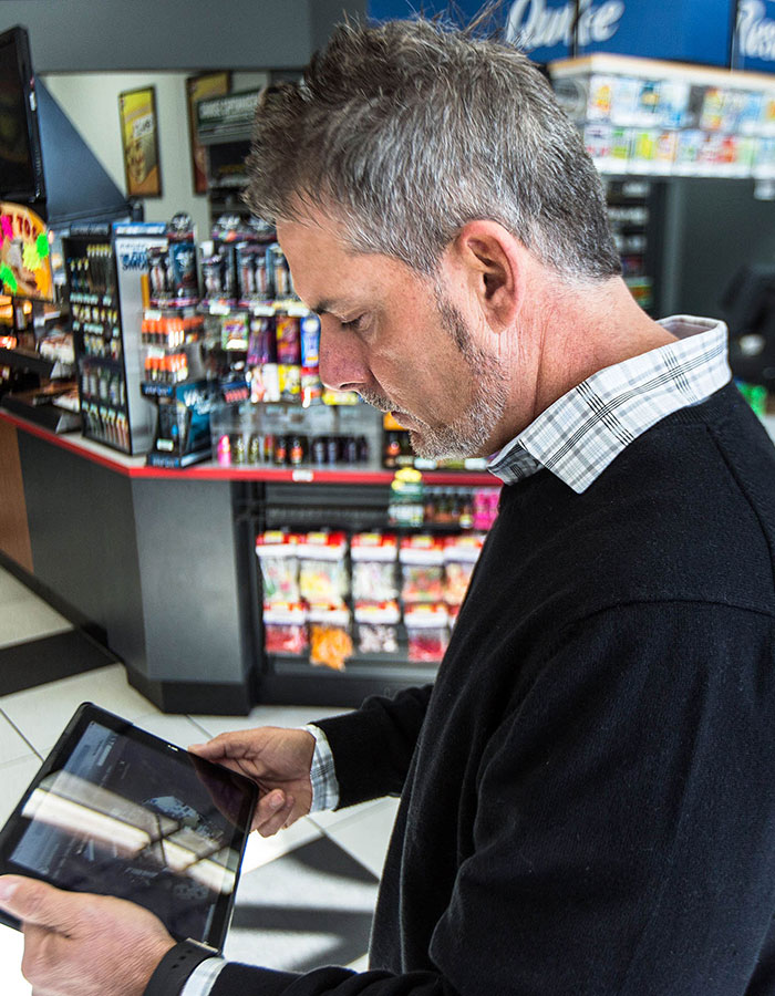 Quik-E food TB Burgess Mobile - Todd Burgess, Vice President of Quick-E Foods, looks at video surveillance on his tablet device.