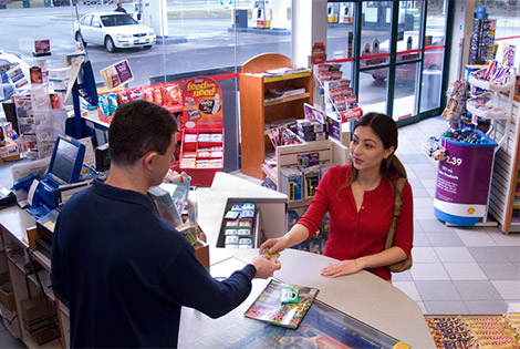 a convenience store employee takes cash from a customer