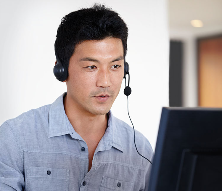 A man with a headset on looking at a monitor