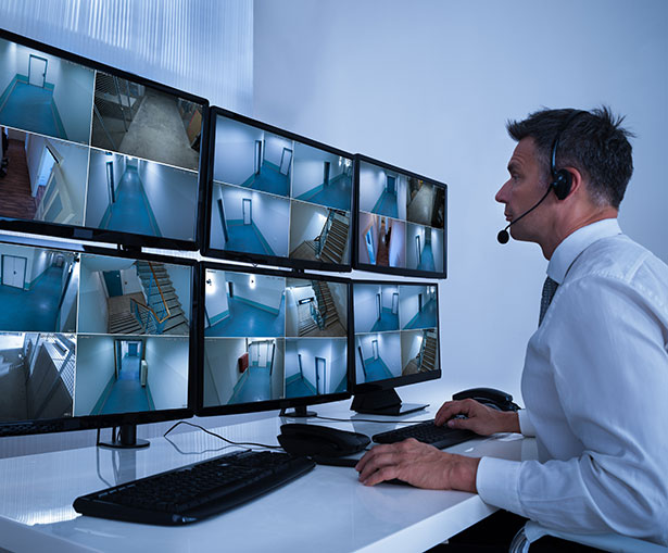 A security officer sits at a desk with multiple monitors displaying video surveillance images.
