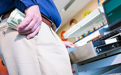 a man stands at a POS terminal and stuffs cash into his pocket