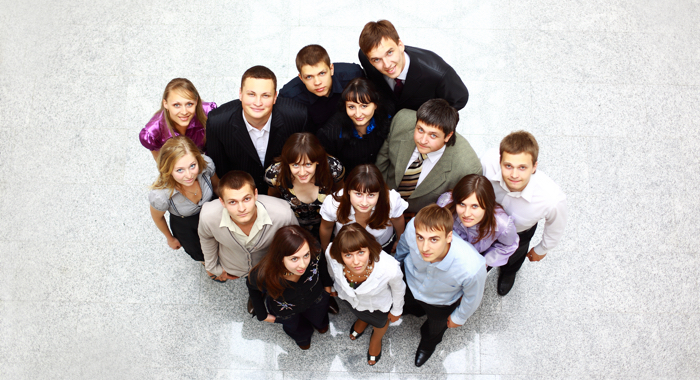 An aerial photo of a group of people looking up into a camera.