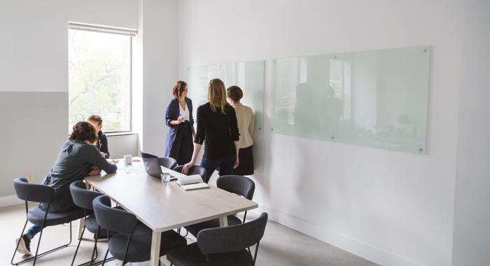 Five people work inside a boardroom