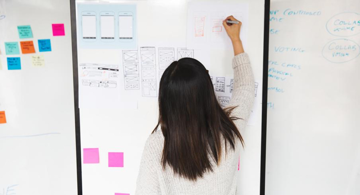 A woman writes notes on a whiteboard