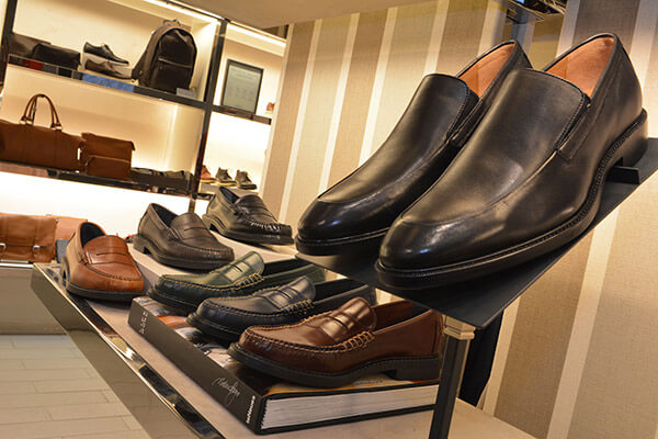 a row of men's shoes inside a Cole Haan location