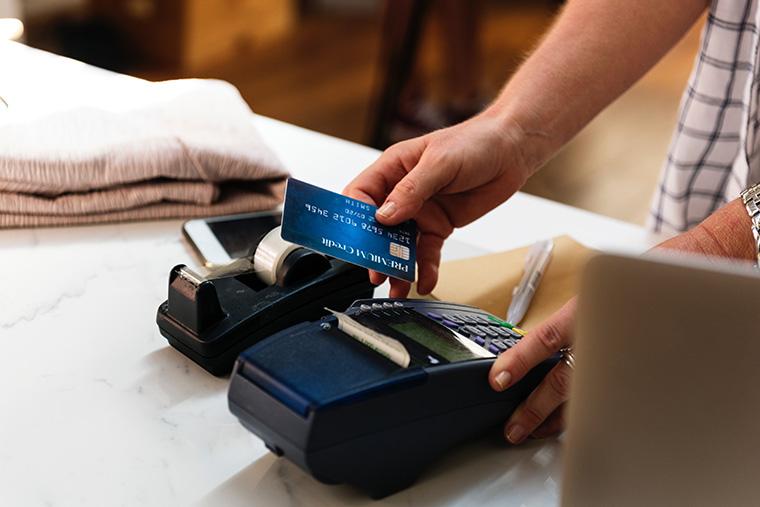 A person swipes a card through a retail debit/credit machine.