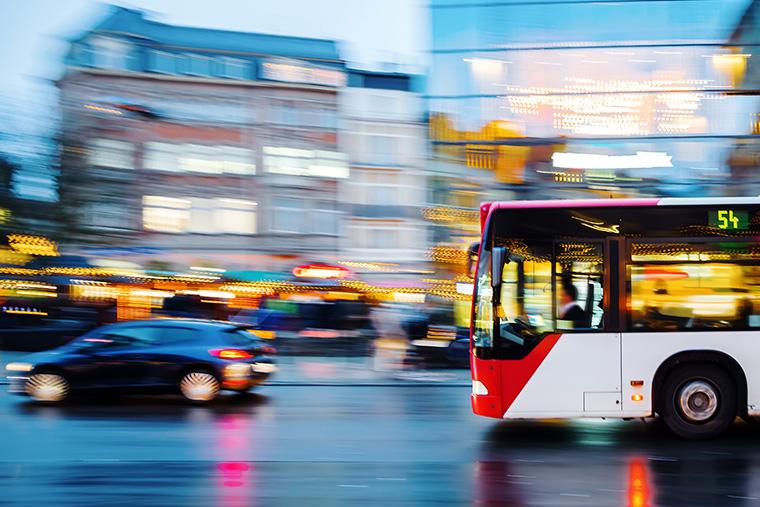 A city bus speeds through a busy street.