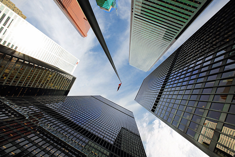 A view from the bottom of several tall city buildings.