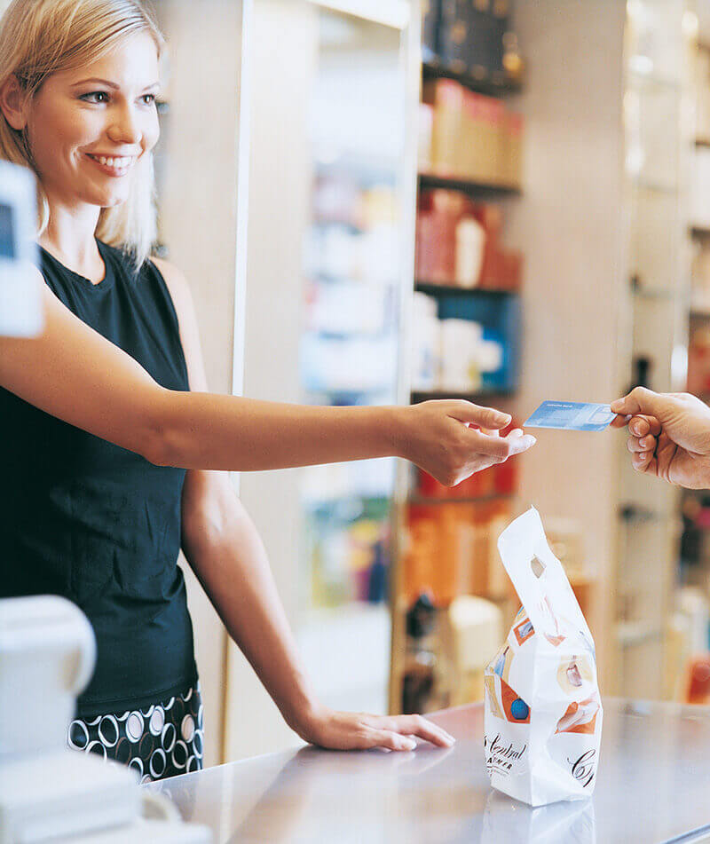 A retail employee accepts a credit card from a customer.