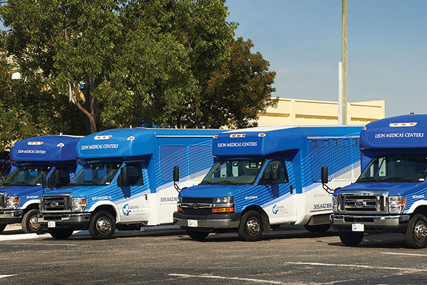 Four Leon Medical Centers buses are parked in a parking lot