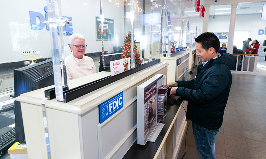A man stands in front of the bank teller counter at Dime Community Bank.