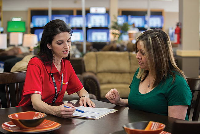 A Rent-A-Center female employee sits at a desk with another woman, doing paperwork.