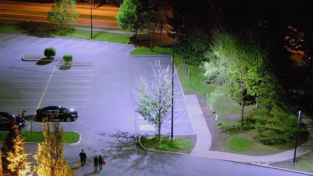 A colorful video surveillance image of a parking lot capture at night