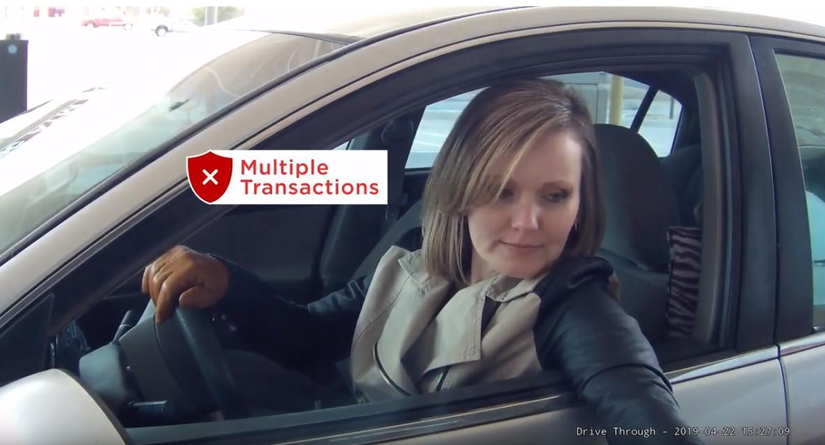 A woman uses a drive-thru ATM