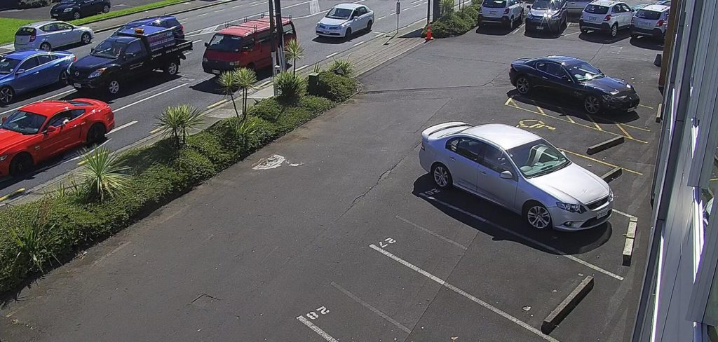 A video surveillance image of a parking lot situated near a busy roadway.