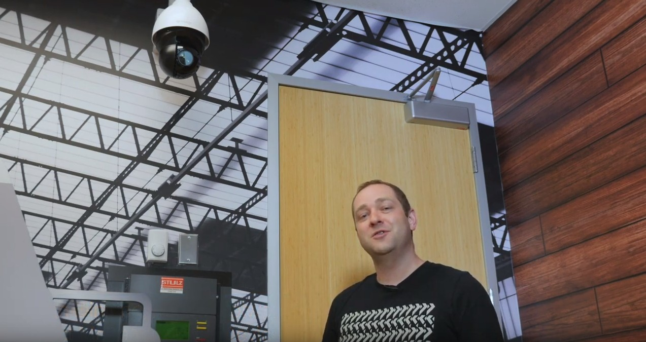 A man stands in a room with a PTZ camera