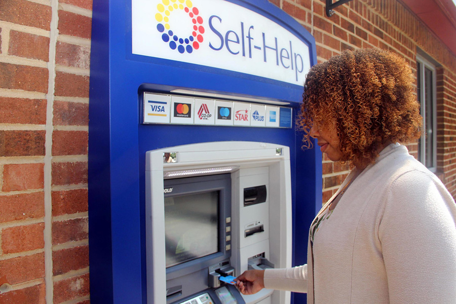 A woman uses a Self-Help Credit Union ATM