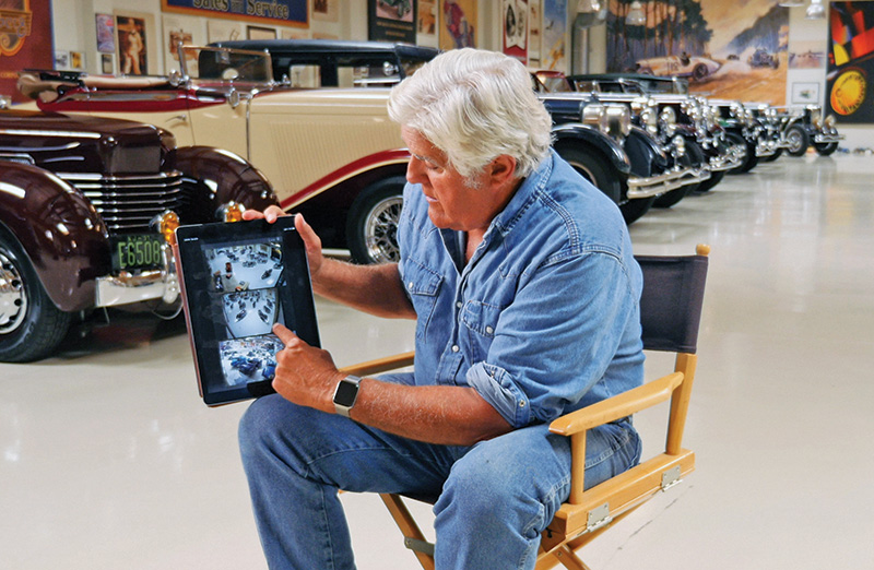 Jay Leno looks at video surveillance images on a tablet