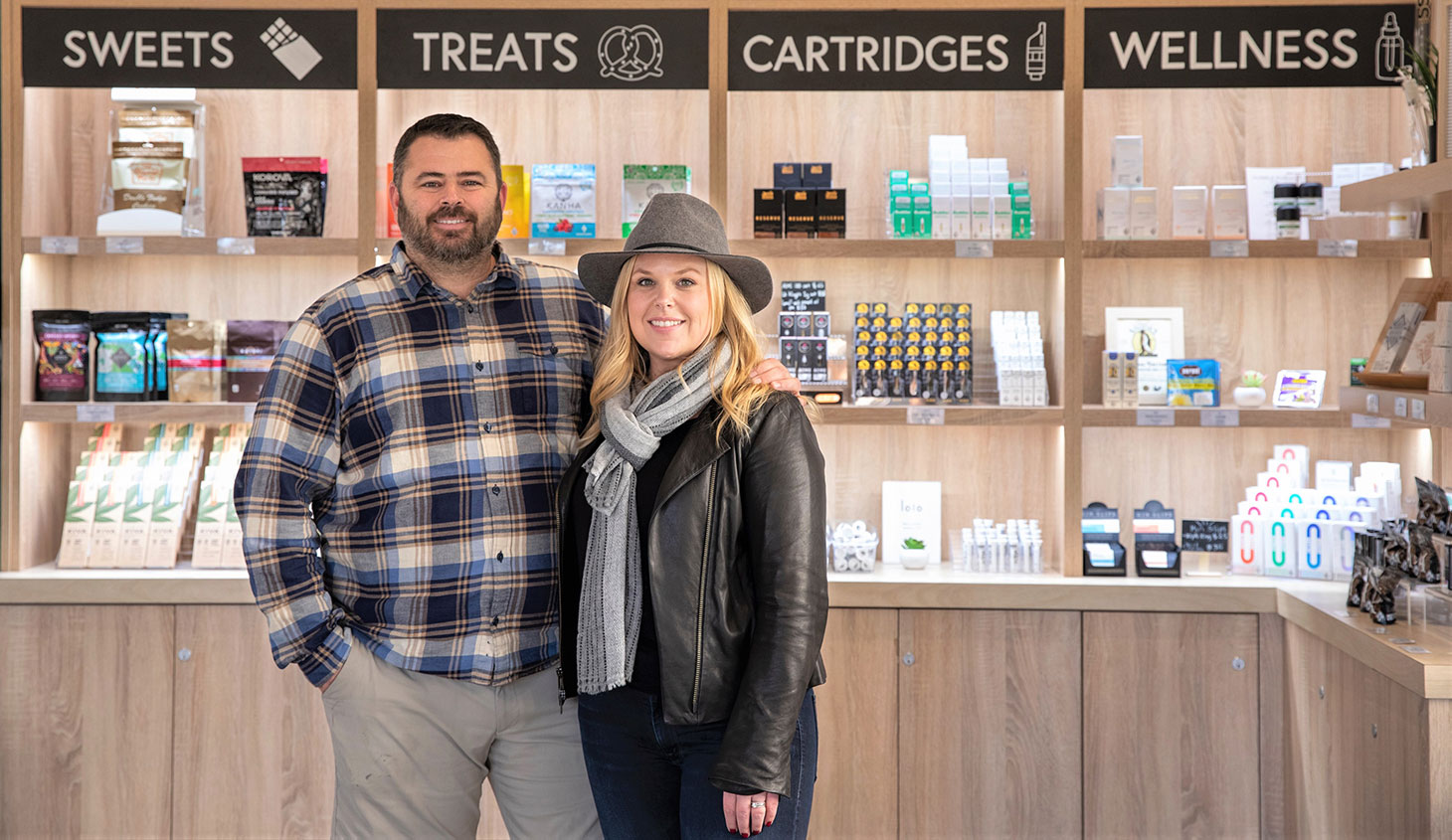 Inside Flora Terra store with owners, David and Alicia Wingard, posing and smiling in front of sign