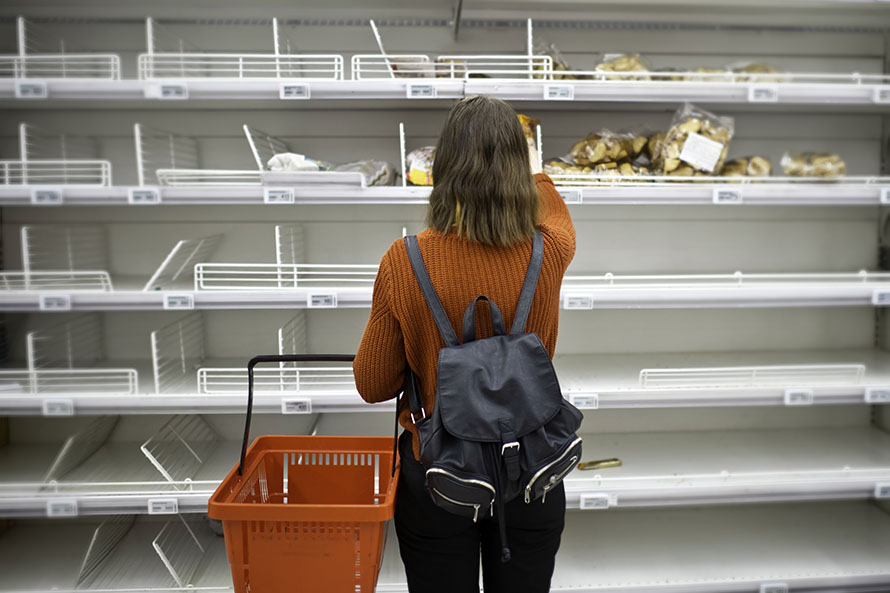 Woman reaching for bread with bare shelves around her.
