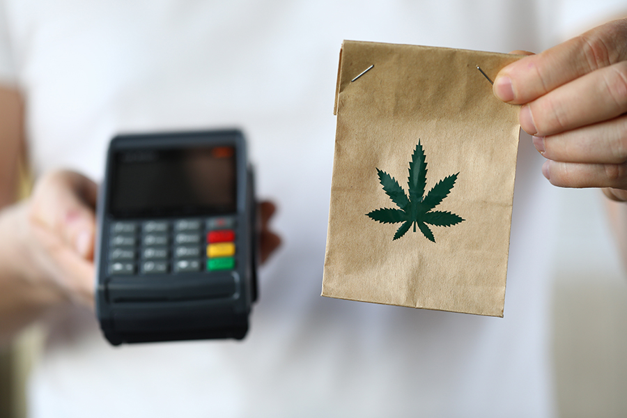 Man holding a point-of-sale terminal and small paper bag with cannabis leaf on it.