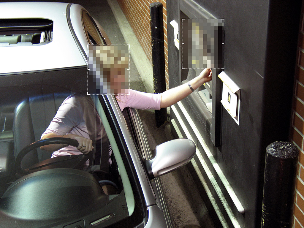 image of a lady in the car inserting card in ATM machine