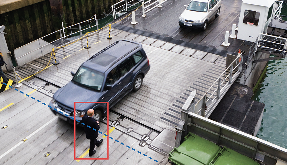 man walking across bridge, showing rectangle around him to signify object identification