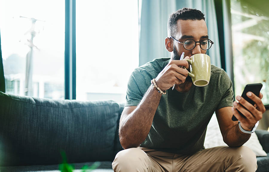 man sipping coffee and checking phone on couch