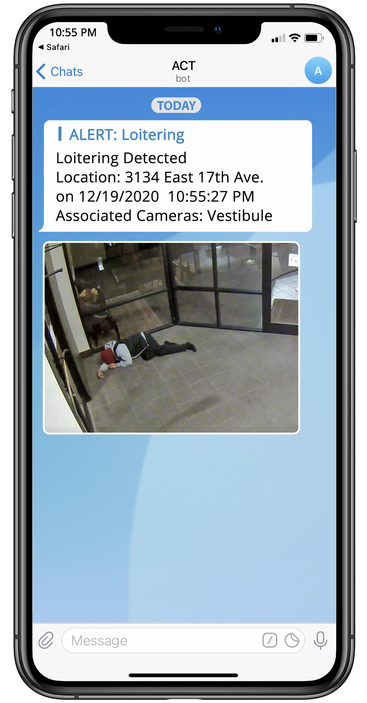man loitering in bank vestibule, alert on mobile