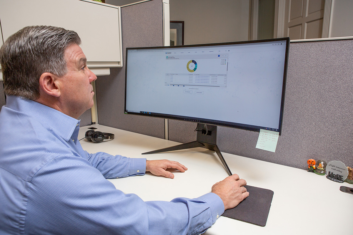 Don Maday, General Manager for Cox Family Stores, using Insight Monitoring and Resolution Service on a desktop computer in an office