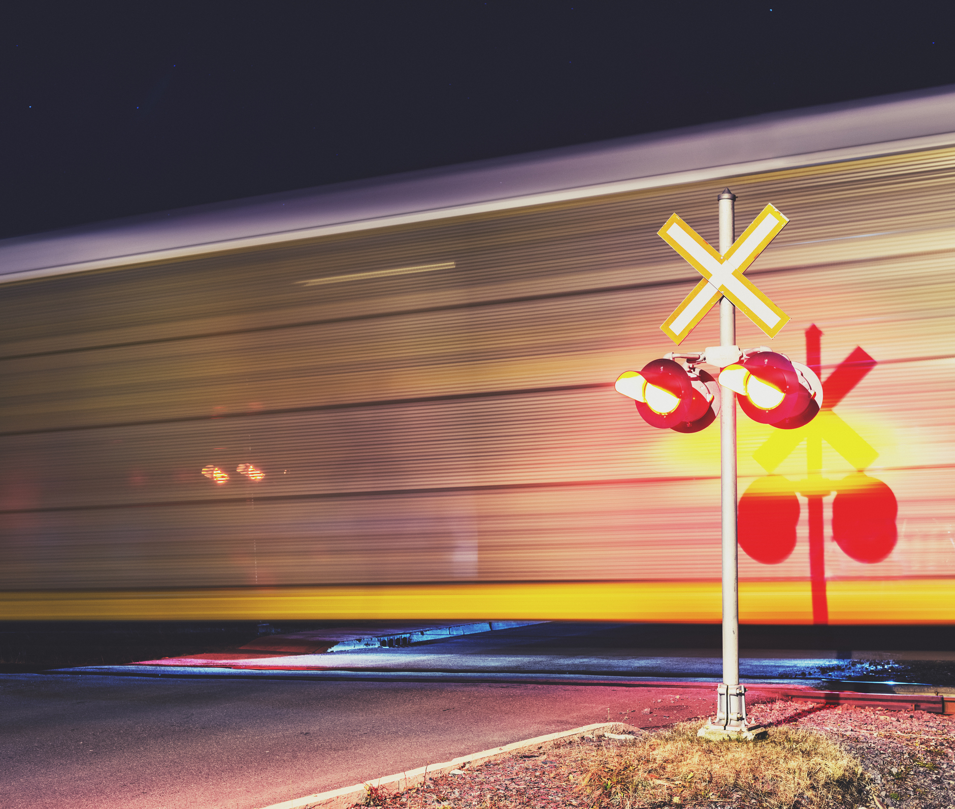 train speeding past on railroad track with railroad sign flashing