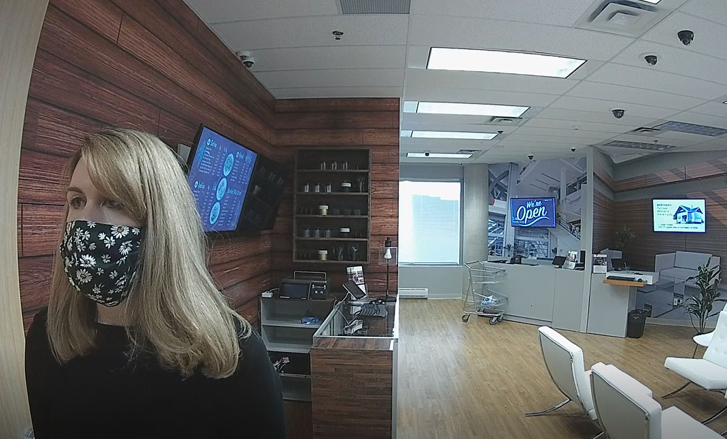 Video snapshot from a covert camera of a person wearing a mask from eye-level view in a retail environment.