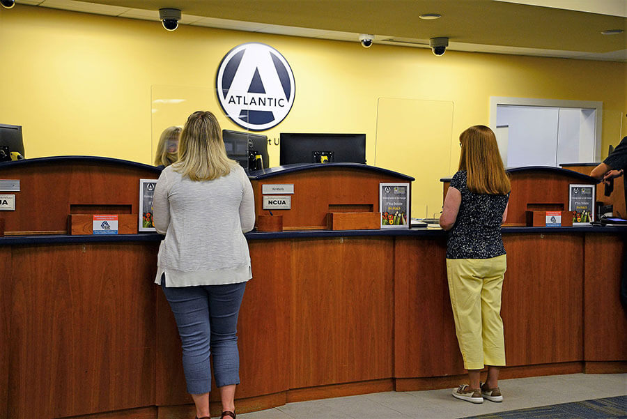 Clients standing in front of a desk speaking with tellers with visible March Networks cameras mounted to the ceiling at an Atlantic Federal Credit Union location